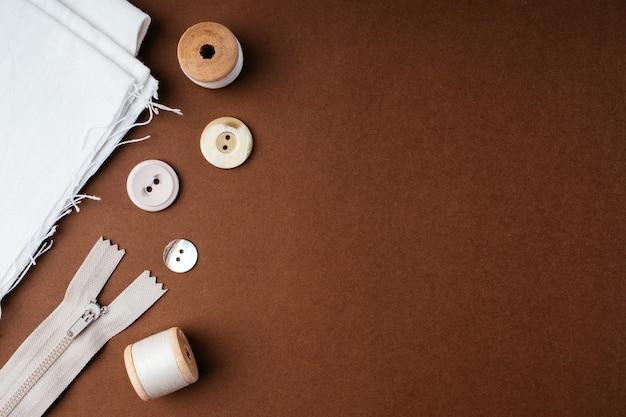 Tkaniny i narzędzia do szycia do robótek ręcznych na brązowym tle, płaski płaski, widok z góry, kopia przestrzeń. tworzenie koncepcji odzieży modowej. poziome tło dla reklamy lub opakowania.