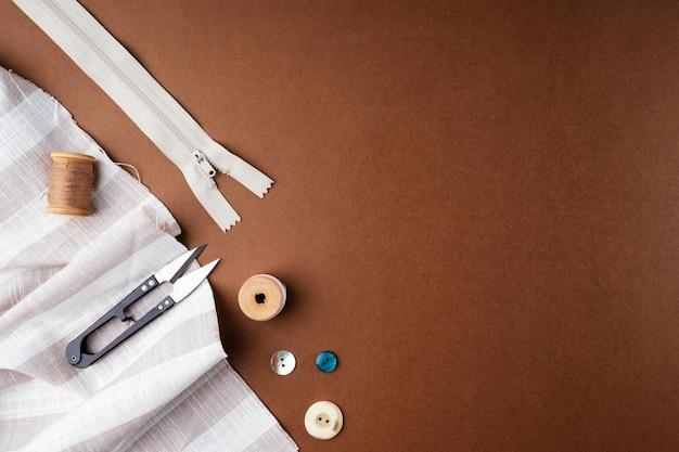 Tkaniny i narzędzia do szycia do robótek ręcznych na brązowym tle, płaskie mieszkanie, widok z góry, miejsce na kopię.