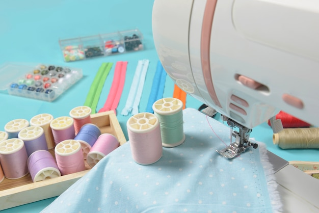 Tkaniny na maszynie do szycia wśród nożyczek, guzików koszulowych, suwaków i rolek z nicią.