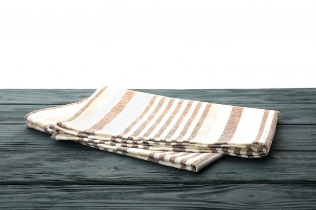 Tkaniny pielucha na stole przeciw białemu tłu, przestrzeń dla teksta