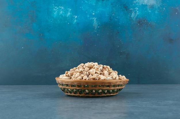 Tkany kosz wypełniony porcją chrupiących płatków kukurydzianych na niebieskim tle. zdjęcie wysokiej jakości