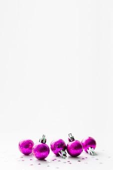 Tła bożych narodzeń i nowego roku z purpurowymi purpurowymi dekoracyjnymi piłkami dla choinki.