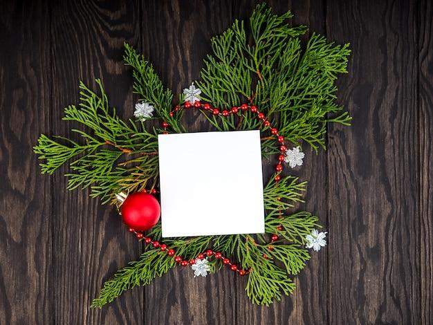 Tła choinki, kreatywny układ wykonany z gałęzi choinki ze śniegiem i kartą papierową. leżał płasko. koncepcja nowego roku natura.