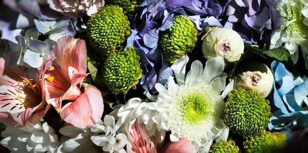 Tle kwiatów. świąteczny bukiet różnorodnych kwiatów, w tym niebieskiej hortensji, różowej alstremerii i zielono-zielonej dalii