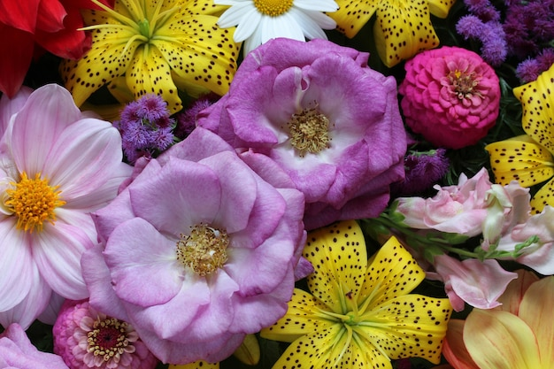 Tle kwiatów z żółtymi liliami i fioletowymi różami