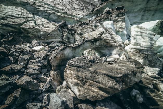 Tle przyrody z lodospadem w pobliżu ściany lodowca z pęknięciami i rysami. naturalne tło z lodową ścianą i blokami lodu. piękny krajobraz z błyszczącą ścianą polodowcową i blokami lodu w słońcu.