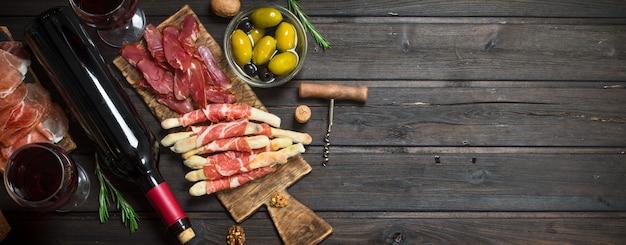 Tło antipasto. różne mięsne przystawki z oliwkami, szynką i czerwonym winem.
