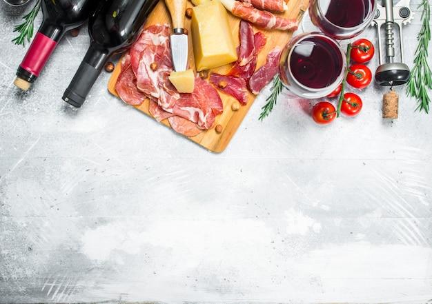 Tło antipasto. różne przekąski mięsne i serowe z czerwonym winem. na rustykalnym tle.