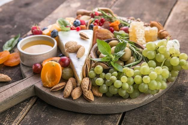 Tło antipasto różne włoskie przekąski z orzechami owocowymi na rustykalnym tle