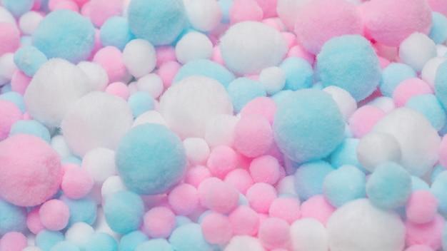 Tło białe, różowe i niebieskie miękkie pompony.