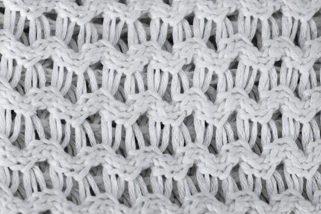 Tło białe wełniane dzianiny. dzianinowe ciepłe ubrania dla zimowej tekstury tkaniny