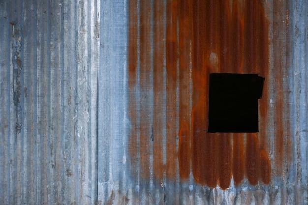Tło blaszanego dachu z dziurą starej rdzy i gwoździ w stylu vintage. blachy ze stali ocynkowanej z rdzą na tle