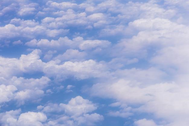 Tło błękitnego nieba z białymi chmurami w słoneczny dzień.