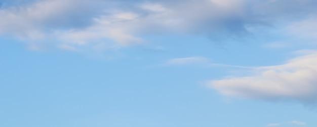 Tło błękitnego nieba z białymi i różowymi chmurami o zachodzie słońca