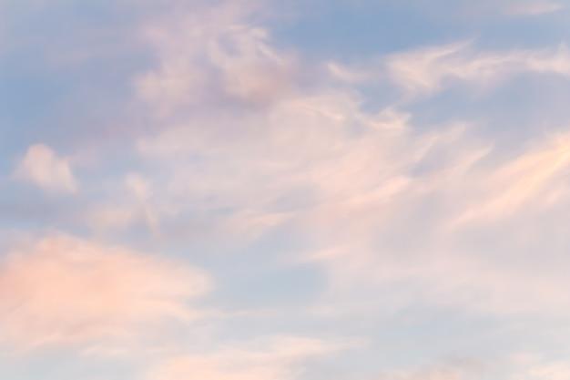 Tło błękitnego nieba z białymi różowymi chmurami o zachodzie słońca