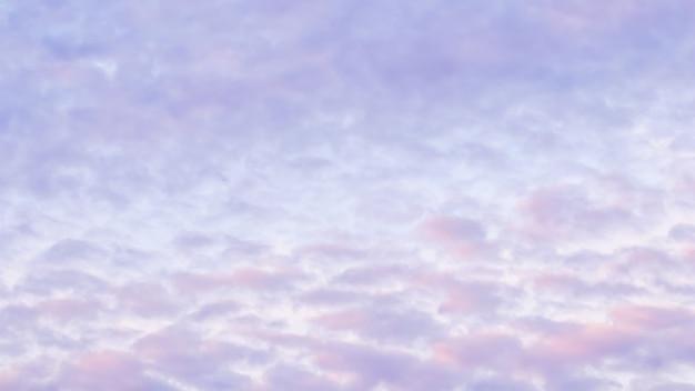 Tło błękitnego nieba z jasnoróżowymi chmurami o zachodzie słońca