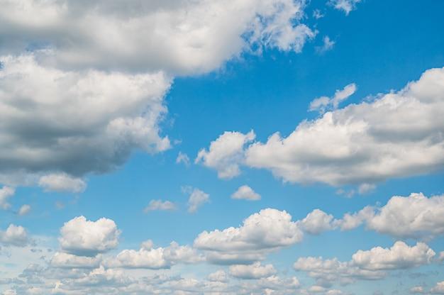 Tło błękitnego nieba z puszystymi chmurami