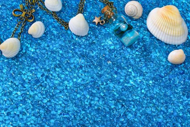 Tło błękitnego oceanu, z muszelkami i ślimakiem na błyszczących kamyczkach dekoracyjnych.