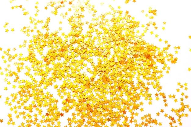Tło błyszczące złote małe gwiazdki, koncepcja boże narodzenie. brokatowa tekstura.