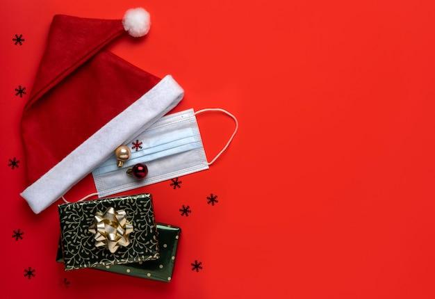 Tło boże narodzenie koronawirusa. czapka świętego mikołaja i świąteczne dekoracje z maską na czerwonym tle.