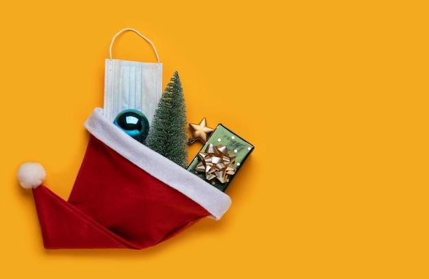 Tło boże narodzenie koronawirusa. czapka świętego mikołaja i świąteczne dekoracje z maską na żółtym tle.