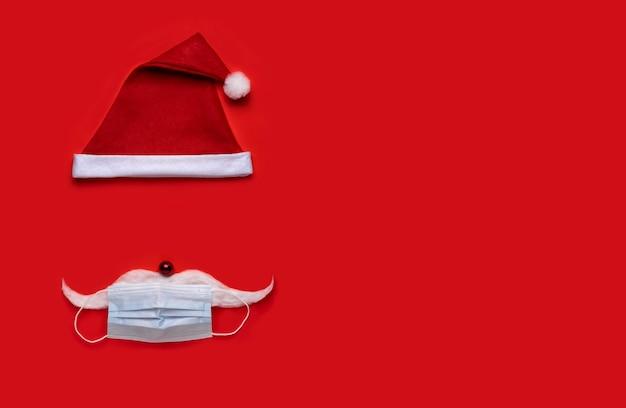 Tło boże narodzenie koronawirusa. czapka świętego mikołaja z maską na czerwonym tle.