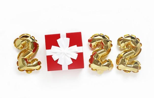Tło bożego narodzenia lub nowego roku tekst 2022 wykonany ze złotych kul i czerwonego prezentu z białą kokardą