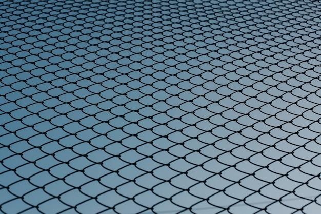 Tło chainlink ogrodzenie z niebieskim niebem w tle. koncepcja tła.