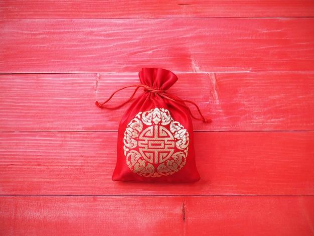 Tło chińskiego nowego roku. czerwony jedwabisty worek na pieniądze ze sznurkiem na tle naturalnego drewna sosnowego i miejsca kopiowania.