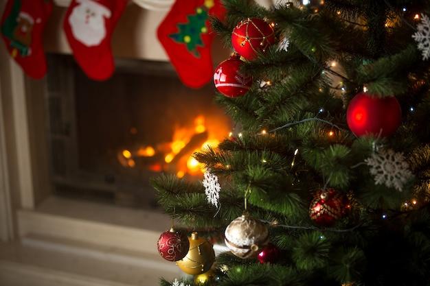 Tło choinki w salonie z płonącym kominkiem ozdobionym tradycyjnymi pończochami na prezenty