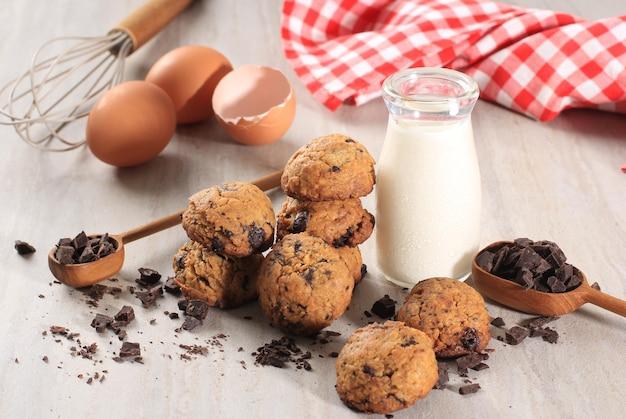Tło ciasteczka czekoladowe z miejsca kopiowania na szarym drewnianym stole. domowe jedzenie/przekąski z mlekiem dla dzieci. wybrany fokus