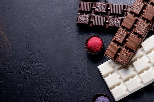 Tło czekoladki. czekolada. asortyment wykwintnych czekoladek w czekoladzie białej, deserowej i mlecznej. praliny czekoladowe słodycze.