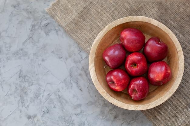 Tło czerwone jabłka. dojrzałe czerwone jabłka w drewnianym pudełku. widok z góry z miejscem na tekst. jabłka w drewnianym talerzu na szarym betonowym stole. koncepcja żywności ekologicznej i zdrowej żywności. dieta surowa żywność, owoce,