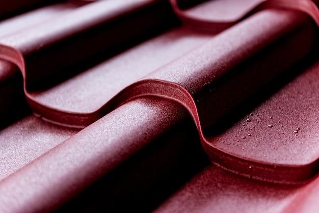 Tło czerwone metalowe dachówki z kroplami wody.
