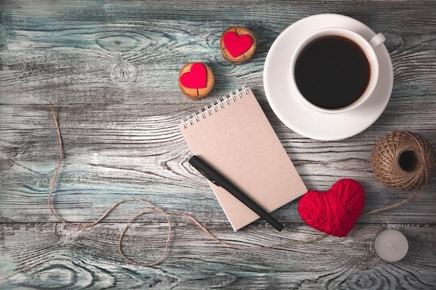 Tło dla 14 lutego z kawą, notatnikiem i sercami na drewnianym tle.