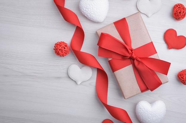 Tło dla karty z pozdrowieniami walentynki. koncepcja walentynki. wstążki czerwony prezent, prezenty, serca na tle drewnianych. widok z góry.