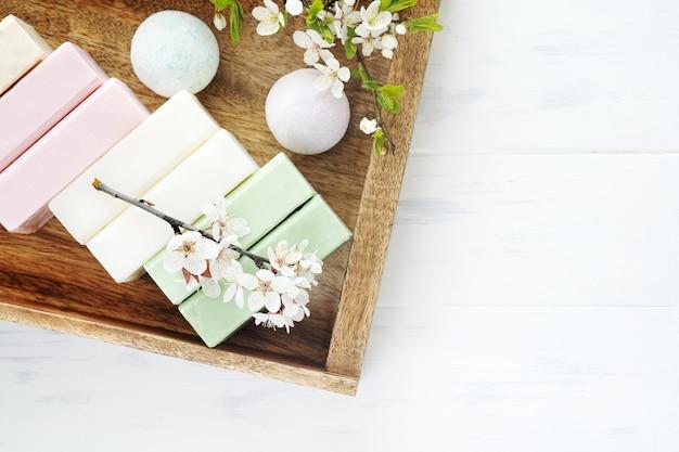 Tło dla mydła spa. aromatyczne mydło naturalne z kwiatami sakury i bombą do kąpieli na drewnianym tle, widok z góry