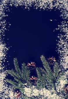 Tło dla nowego roku pozdrowienia z gałęzi drzew, szyszek i śniegu