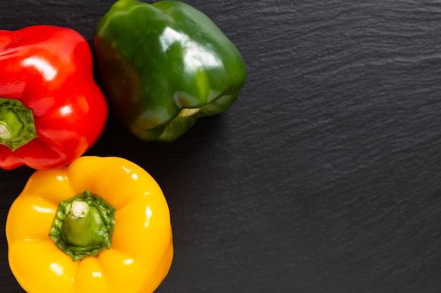 Tło dla produktu spożywczego 3 kolory czerwony zielony i żółty organiczny papryka lub parpika na czarnej tabliczce łupkowej