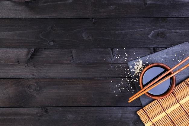 Tło dla sushi. mata bambusowa i sos sojowy na czarnym drewnianym stole. widok z góry z miejscem na kopię