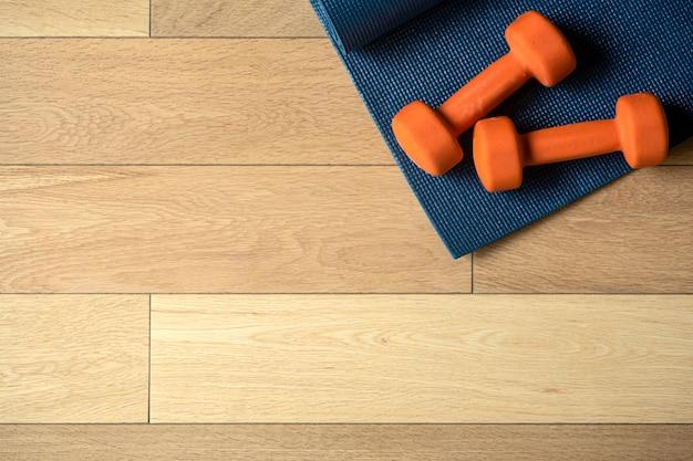 Tło do jogi i fitnessu drewniana podłoga parkiet lub laminat z dywanikiem i hantlami