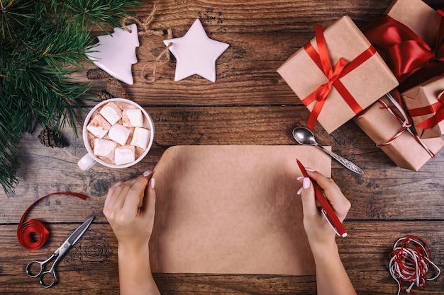 Tło do pakowania prezentów. kobiece ręce pakujące ręcznie robione ozdoby świąteczne na świąteczny prezent w papierze pakowym