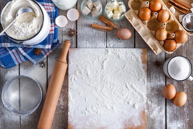 Tło do pieczenia. gotowanie składników do wyrobu ciasta i ciasta i posypane mąką deską na rustykalnym drewnie. widok z góry