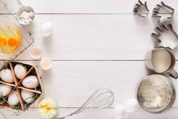 Tło do pieczenia. gotowanie składników na ciasto i ciasto, jajka, mąkę i foremkę do ciastek na białym rustykalnym drewnie. widok z góry