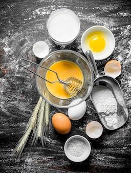 Tło do pieczenia. mąka z mlekiem, jajkami i kłoskami na rustykalnym stole