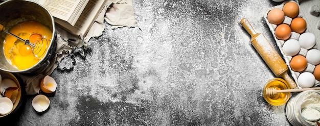 Tło do pieczenia. różnorodne składniki z książki kucharskiej. na tle rustykalnym.