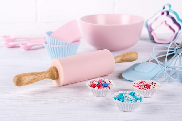 Tło do pieczenia za pomocą narzędzi kuchennych: wałek do ciasta, drewniane łyżki, trzepaczka, sito, naczynia do pieczenia i kształt foremki do ciastek na białym tle drewnianych.