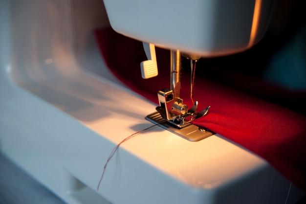 Tło do szycia hobby. maszyna do szycia z czerwonego materiału. zamknij proces z miejsca kopiowania. dramatyczne ciemne kolory.