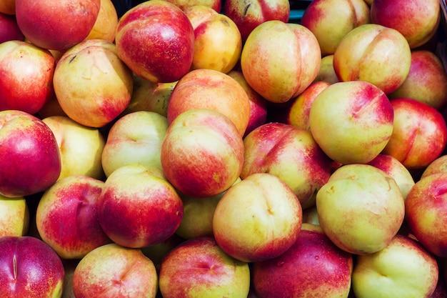 Tło dojrzałe nektaryny w ulicznym rynku.