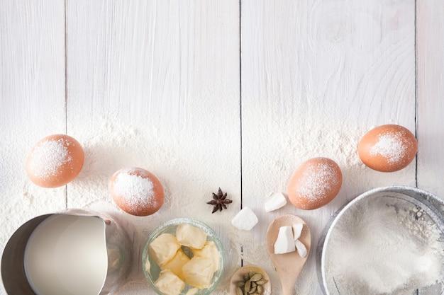 Tło domowej roboty piekarni. składniki do pieczenia na drewnianym stole kuchennym - masło, jajka, mąka i przyprawy